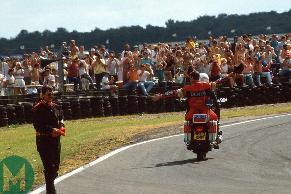 Nigel Mansell returns to the pits on a moped after winning the 1987 British Grand Prix
