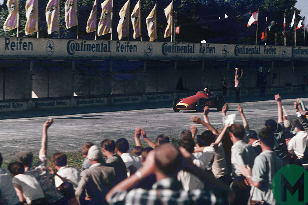 Juan Manuel Fangio takes the applause on the way to winning the 1957 German Grand Prix