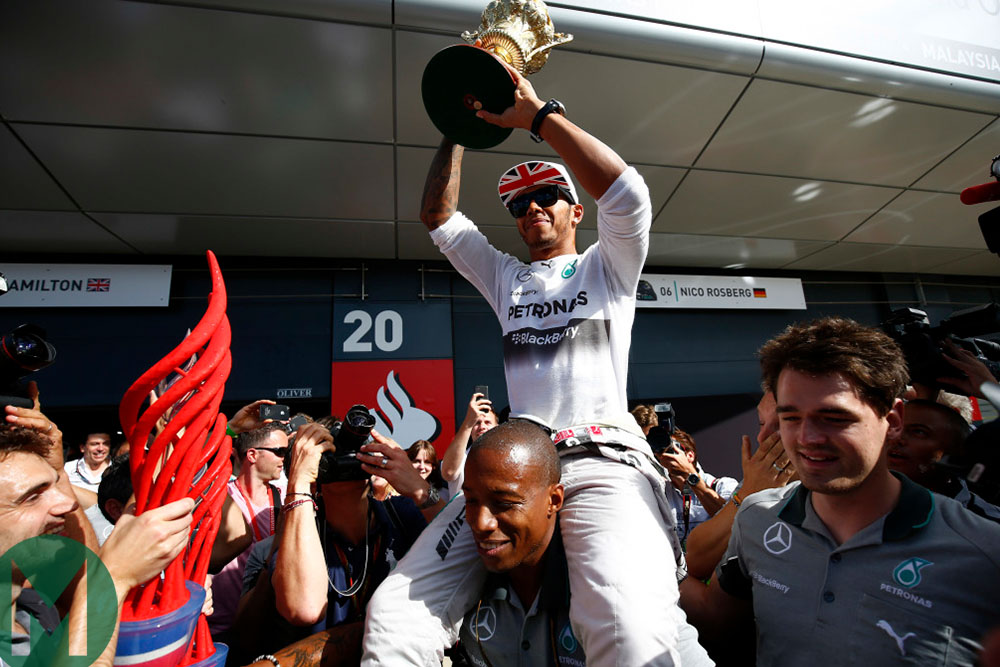 Lewis Hamilton holds the 2014 British Grand prix-winning trophy aloft