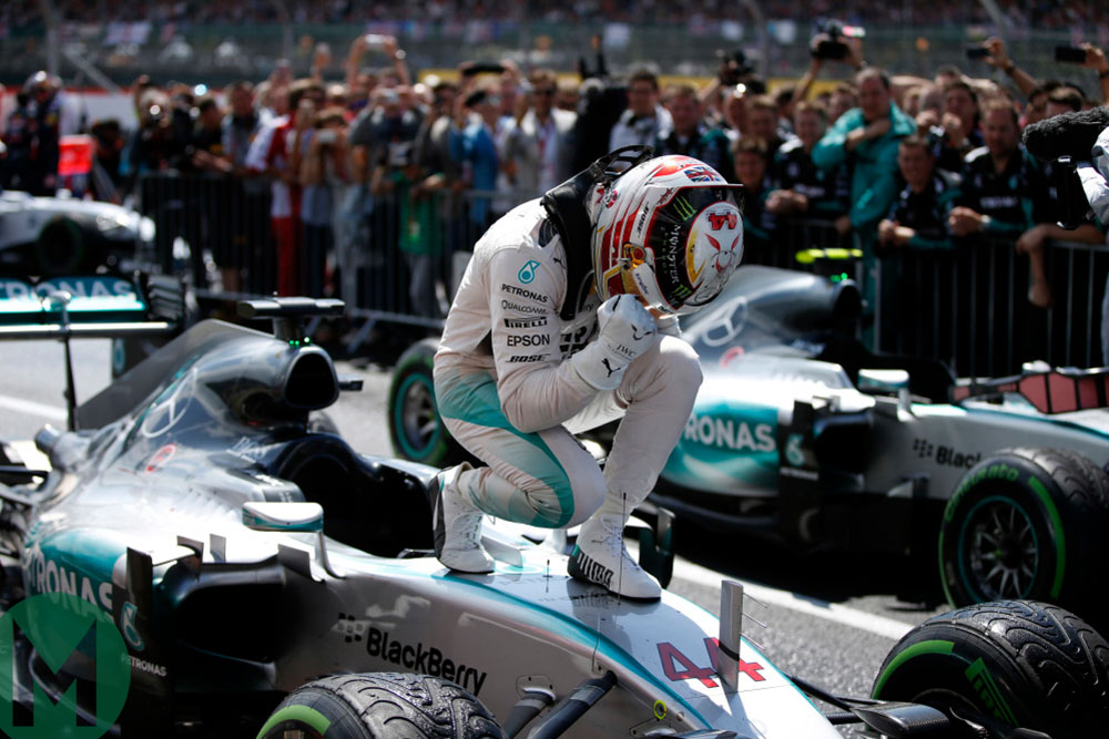 Lewis Hamilton crouches over his Mercedes after winning the 2015 British Grand Pris at Silverstone