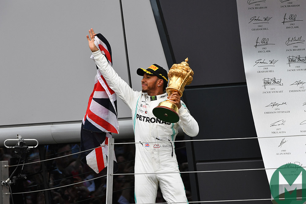 Lewis Hamilton holds the race-winning 2019 British Grand prix trophy and Union jack on the podium