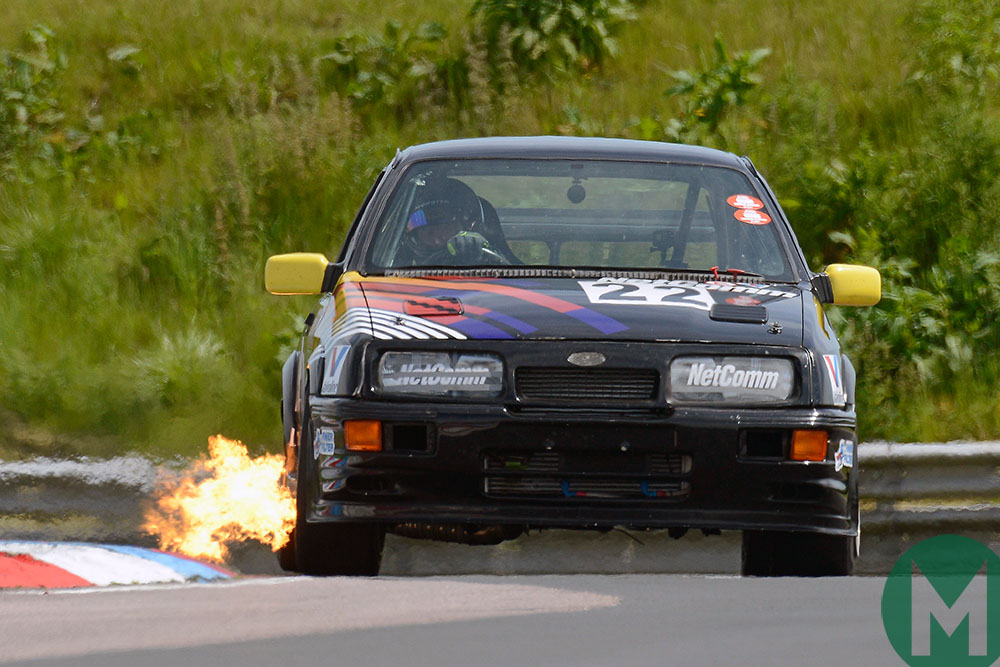 Flames burst from the exhaust of a Ford Sierra at the 2019 Thruxton Classic
