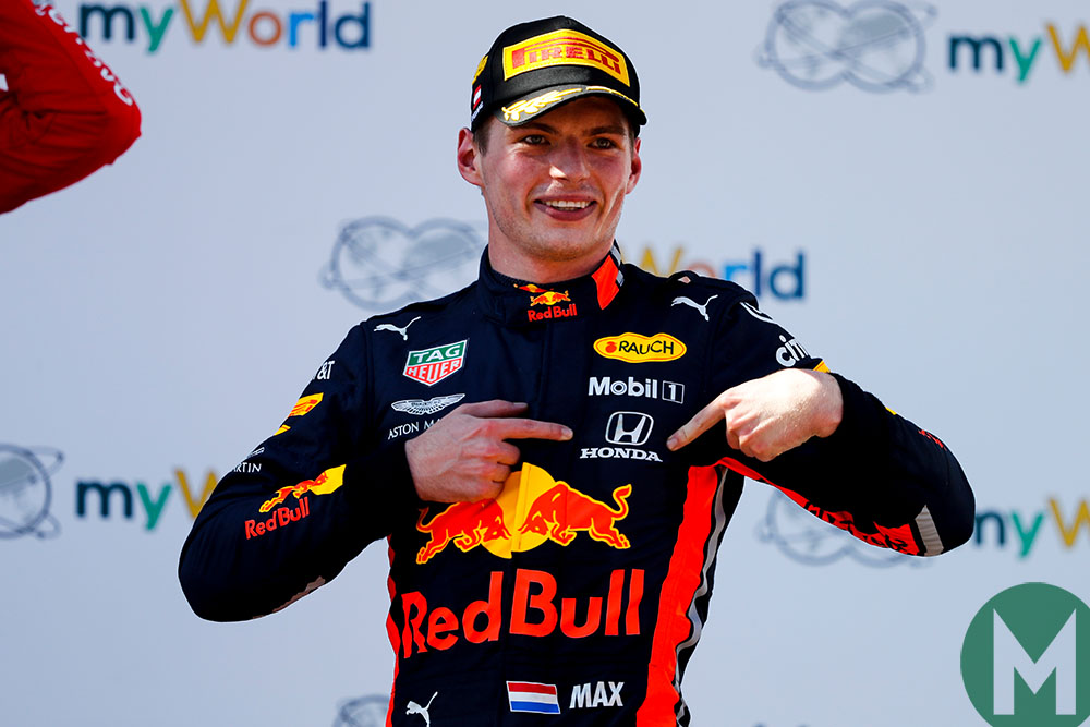 Max Verstappen points to the Honda logo on his overalls after winning the 2019 Austrian Grand Prix