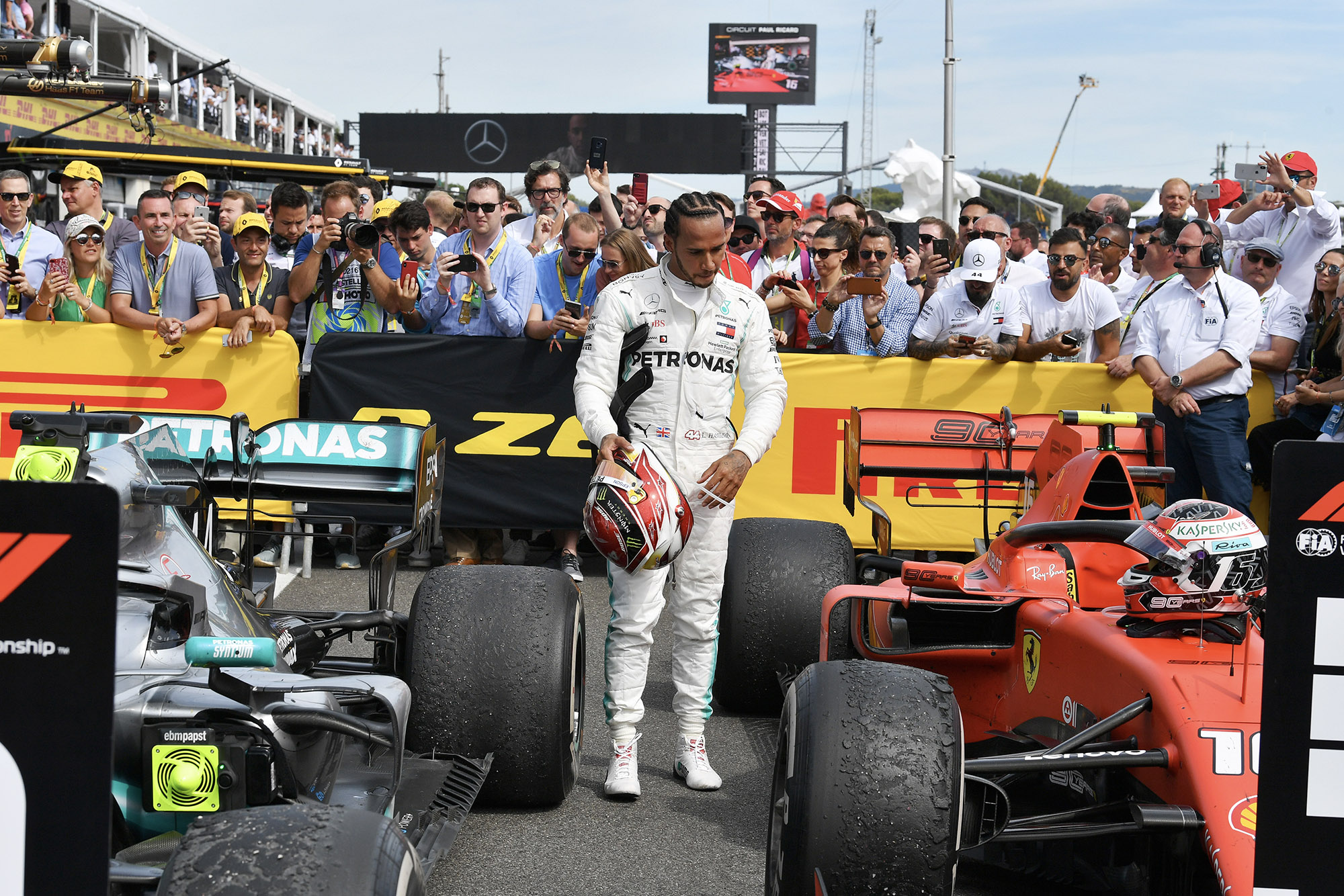 Lewis Hamilton looks at Charles Leclerc's Ferrari after the 2019 French Grand prix