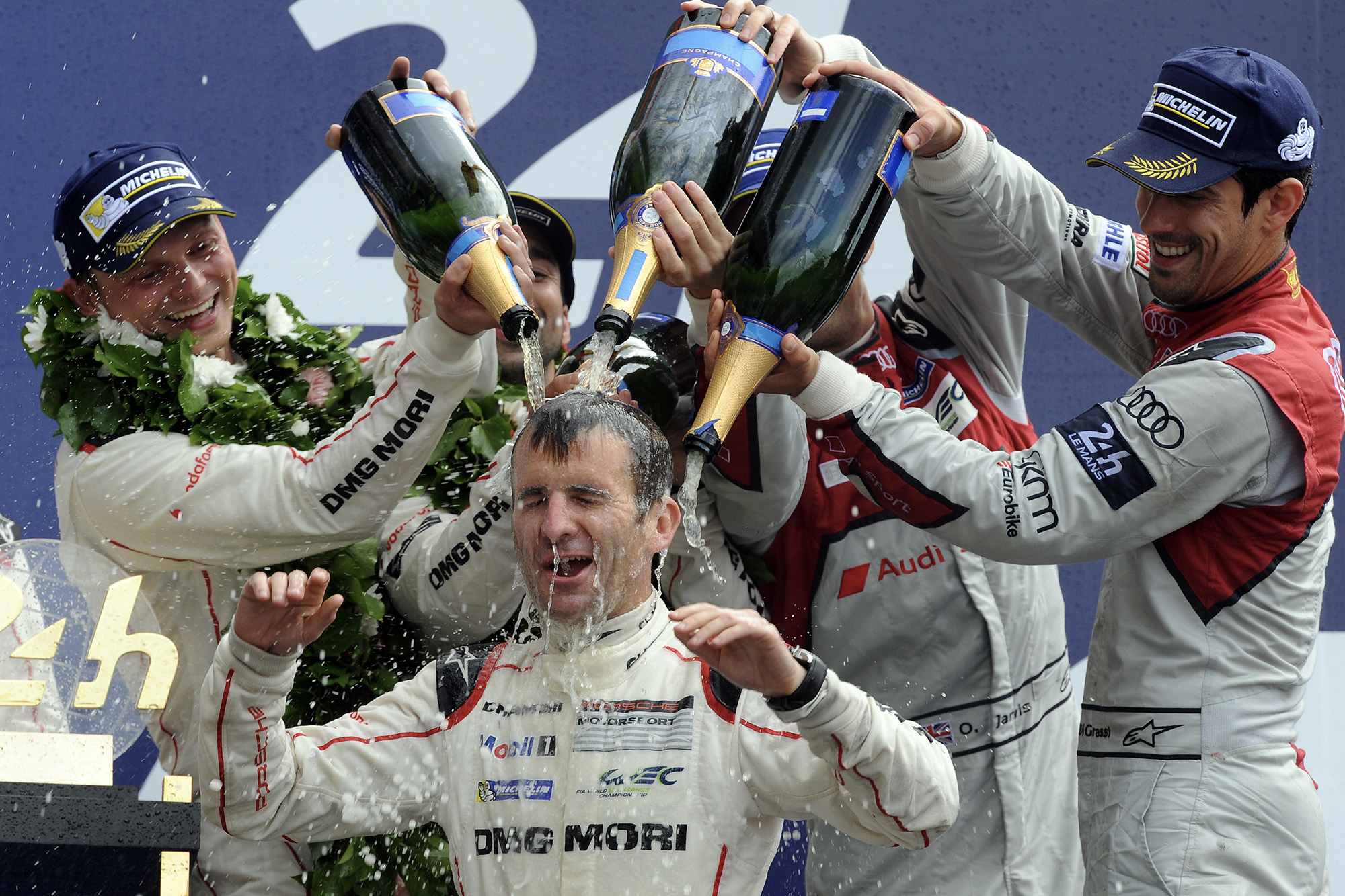 Romain Dumas drenched in champagne on the podium at Le Mans in 2016